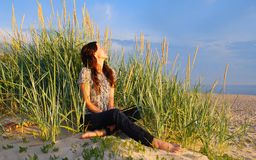 Relax. Young girl sitting on the sand dunes among the grass . The beach of Baltic sea Stock Photography