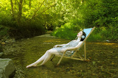 Relax. Young woman lying on a deckchair in a stream and listening to music Royalty Free Stock Photos