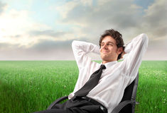 Relax. Young businessman sitting on a chair on a green meadow Royalty Free Stock Photo