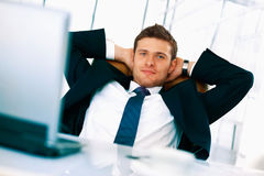 Relax. Young bussinessman sitting relaxed in his chair with hands under his head Stock Photography