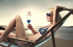Relax. Beautiful woman lying on a deckchair at the beach and holding a glass of cocktail Royalty Free Stock Images