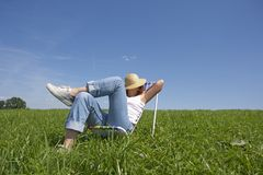 Relax. Young woman lies in a deckchair in the sun Stock Images