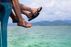 Relax. Tourist's feet hanging on a boat while traveling Royalty Free Stock Image