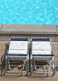 Relax. Two deck chairs beside a swimming pool Stock Photos