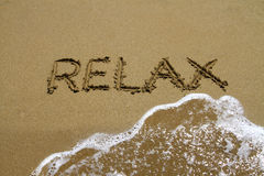 Relax. The word relax written in sand, right before the water wipe the letters away royalty free stock photos