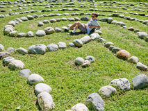 Relax. A boy relaxes inside a Zen Spirit garden maze, Path of Life Garden, Windsor Maine royalty free stock photo