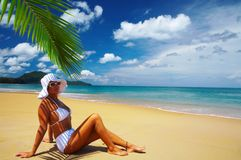 Relax. View of nice woman lounging on tropical beach in white panama and bikini Royalty Free Stock Image