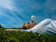 Relax. A woman rests on the grass on a peacefully sunny day Stock Photo
