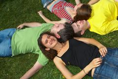Relax. Group of four teenagers laying on a green grass Stock Photo