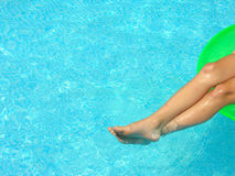 Relax. A young child relaxes her legs on a float in a pool Royalty Free Stock Photos