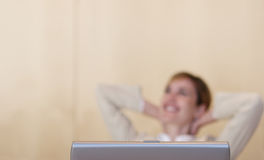 Relax. Young businesswoman works on laptop with arms back of her head Stock Images