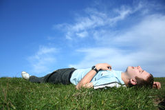 Relax. Yoing boy relaxing on grass Stock Images