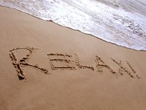 Relax. The word relax written in the sand on the beach royalty free stock image