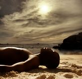 Relax. Black man laying on the beach Stock Photos