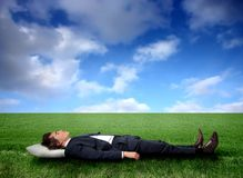 Relax. Business man sleeping on a grass field Royalty Free Stock Image