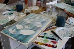 Atelier still life - a painting in progress, aquarelle colours, brushes, jars with water and other objects. Relax with art therapy - preparation for aquarelle stock photography