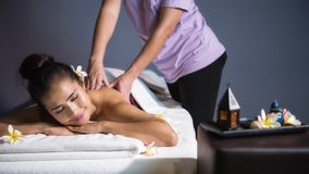 Thai oil massage in spa. Relax Asian beautiful tan woman with white Plumeria in spa. Body care treatment by Thai oil massage. Cute girl having back spiral cure Royalty Free Stock Image