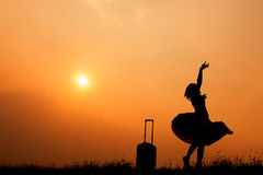 Relax Asian woman with a suitcase on a meadow at sunset silhouette.Holiday travel concept Stock Image