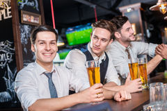 Relax in the bar after a hard work. Four friends men drinking be Stock Image