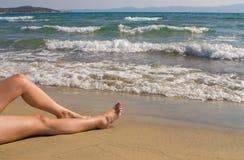Relax on beach. Women's legs resting on sandy tropical beach Stock Photo