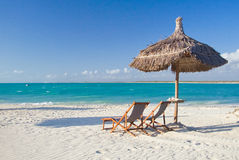 Relax on the beach. Deck chair, parasol and lagoon Royalty Free Stock Photos
