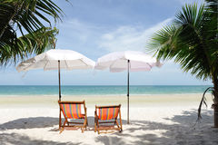 Relax on the beach. White umbrella and shairs on sand beach in tropic royalty free stock photos