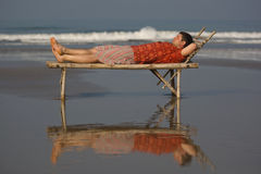 Relax on the beach. Man is lieing on the trestle-bed with a smile on the beach Stock Image