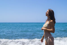 Relax on beach. Beautiful tanned girl and deep blue sea, Ischia island Stock Images