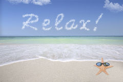 Relax On The Beach. Conceptual of a beach with turquoise water, and the word relax in clouds format, in the sky royalty free stock photos
