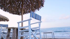 Relax on the beach in a deckchair under an umbrella. Listen to the sound of the sea stock video footage
