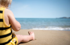 Relax on the beach. Portrait of small baby feet on a sand Stock Images