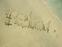 Relax on the beach sand. Relax written on the beach sand stock image