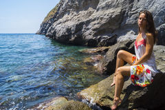 Relax on beach Sorgeto. Beautiful tanned girl and deep blue sea in Sorgeto harbor, Ischia island Royalty Free Stock Image