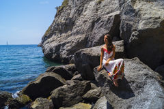 Relax on beach Sorgeto. Beautiful tanned girl and deep blue sea in Sorgeto harbor, Ischia island Royalty Free Stock Photo