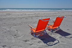 Relax at the beach. Two empty bright orange beach chairs on the sand waiting for their owners to arrive Stock Photography