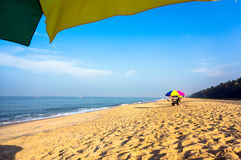 Relax on the beach under umbrellas in the shade. Beach chairs on the white sand beach with cloudy blue sky and sun. Royalty Free Stock Photo