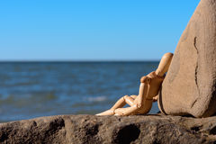 Relax on the beach. Wooden dummy sitting on the stony coast Stock Images