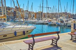 The bench in port of Birgu, Malta. Relax on the bench in Xatt Il-Forn promenade with a view on sailing yachts in port and old quarters of Senglea L-Isla, Birgu Stock Image