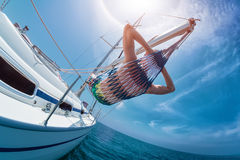 Relax on the boat. Man relaxing in the hammock set on the sail boat while sailing in the open sea Stock Photos