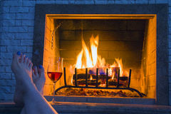 Relax at the burning home fireplace - female legs and a glass of wine. Evening atmosphere stock photo