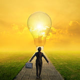 Relax business woman holding bag on Concrete road to Big idea bulb in Grass fields and sunset Stock Photos