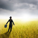 Relax business woman holding bag in yellow rice field and rainclouds Royalty Free Stock Photos
