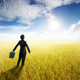 Relax business woman holding bag in yellow rice field and sun sky. Relax business woman standing and holding bag in yellow rice field and sun sky Stock Photo