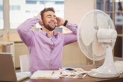 Relax businessman sitting by electric fan Royalty Free Stock Photo