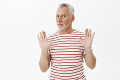 Relax and chil I got it. Portrait of intense questioned charismatic mature man with grey hair and beard raising palms in. Surrender rejecting offer being royalty free stock image