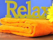 Relax. Closeup from a word relex on an orange bath towel on a wooden underground Royalty Free Stock Image