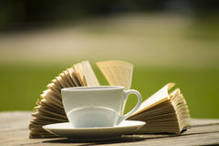 Relax with coffe and book. Opened book with coffe or tea outdoor stock images