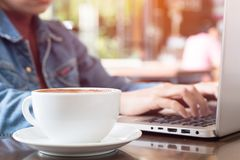 Relax in coffee shop. Close up white cup on wooden table in coffee shop with blurry asian woman typing laptop keyboard, relaxation concept stock photography