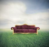 Relax and comfort. Concept of relax and comfort with a velvet red sofa in a green field royalty free stock image