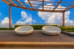Relax corner on condominium rooftop garden with chairs on blue sky background Stock Image